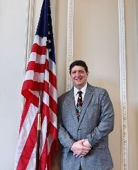 Chairman Kevin Ensley standing beside American flag